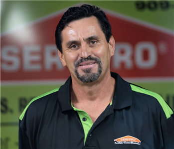 a guy in front of a green SERVPRO truck