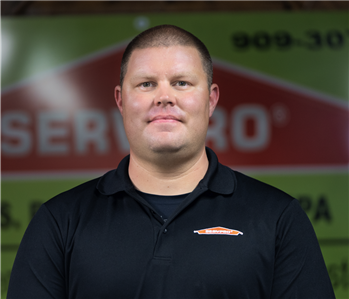 a guy in front of a green SERVPRO background