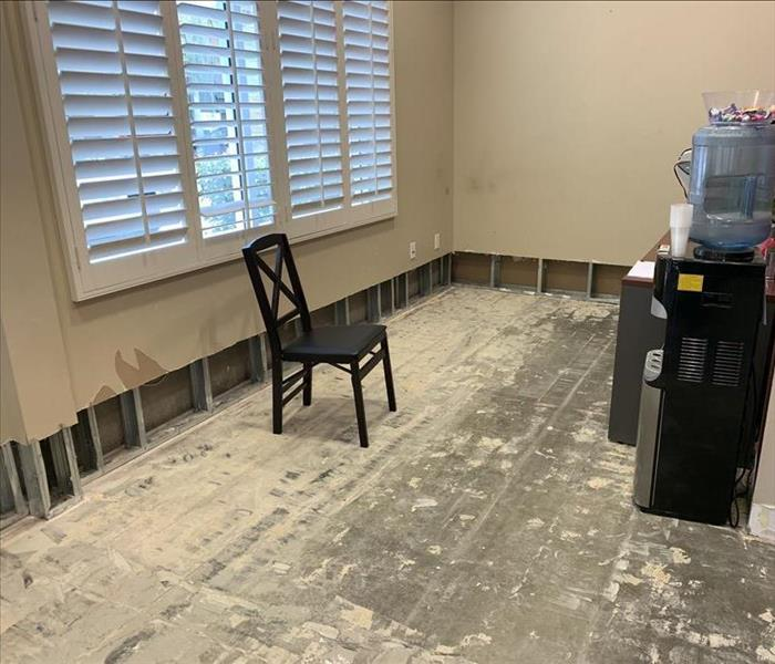 Room with flood cuts and a chair on the floor.