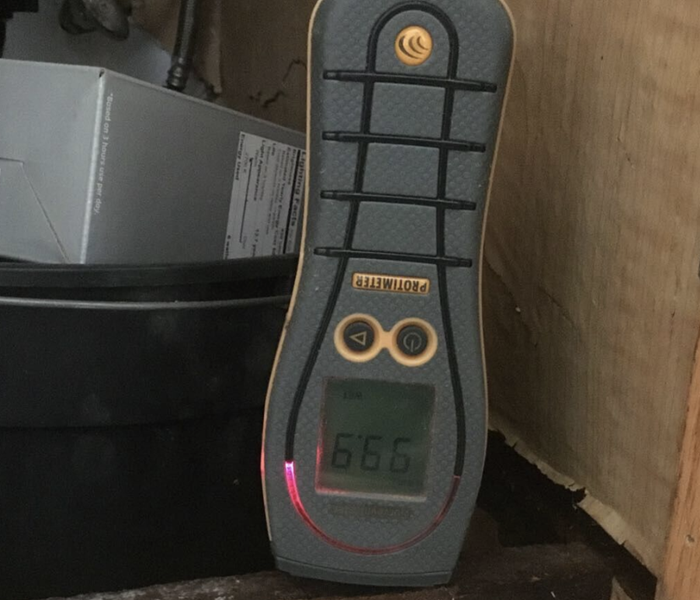 a moisture meter set up in a cabinet space