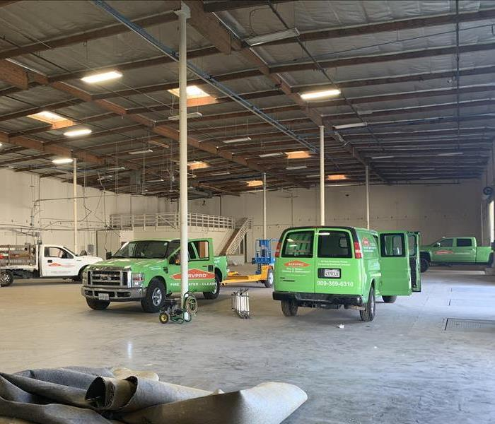 SERVPRO vehicles parked inside a large and empty commercial warehouse.